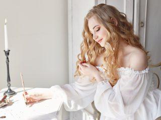 une femme aux longs cheveux blonds est assise et écrit une lettre