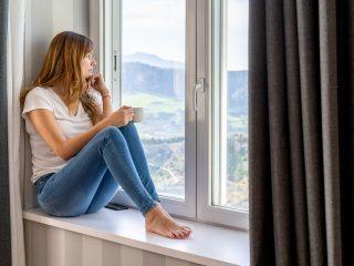 une femme imaginaire est assise près de la fenêtre tenant une tasse à la main