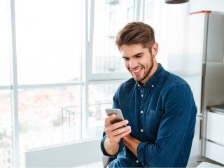 un homme souriant avec un téléphone à la main