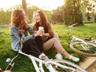 deux amis souriants assis sur l'herbe et riant