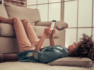 femme allongée sur le sol et bouton sur le téléphone