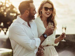 un couple souriant amoureux debout tout en tenant des verres à vin