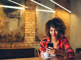 Jeune femme au café de boire du café et à l'aide de téléphone mobile