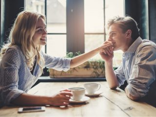 un homme et une femme sont assis à une table, il lui baise la main
