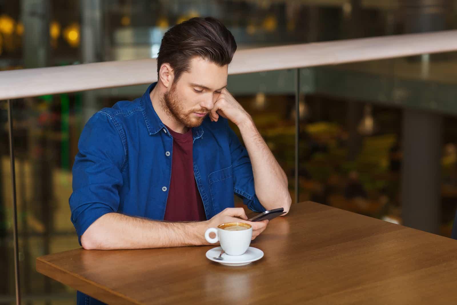 Un homme déçu assis dans un restaurant de boire du café et d'appuyer sur un téléphone