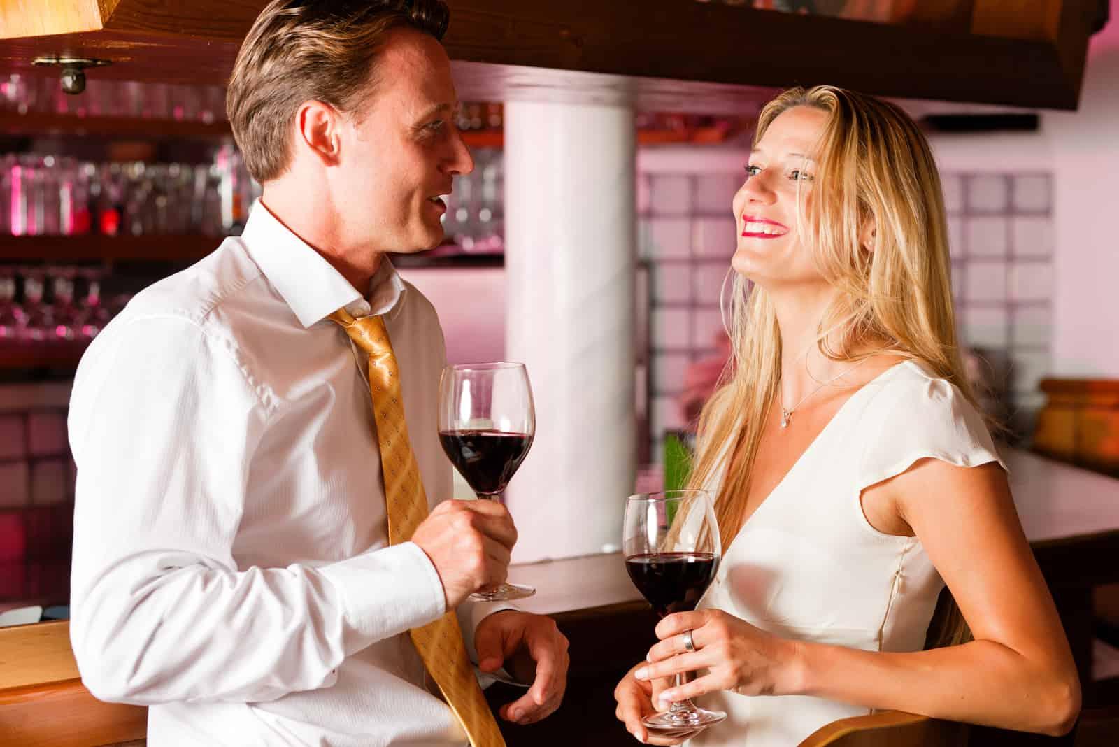 Un homme et une femme souriants se tiennent debout et parlent avec des verres de vin dans leurs mains