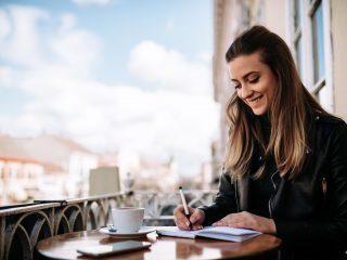 une femme souriante est assise à écrire une lettre