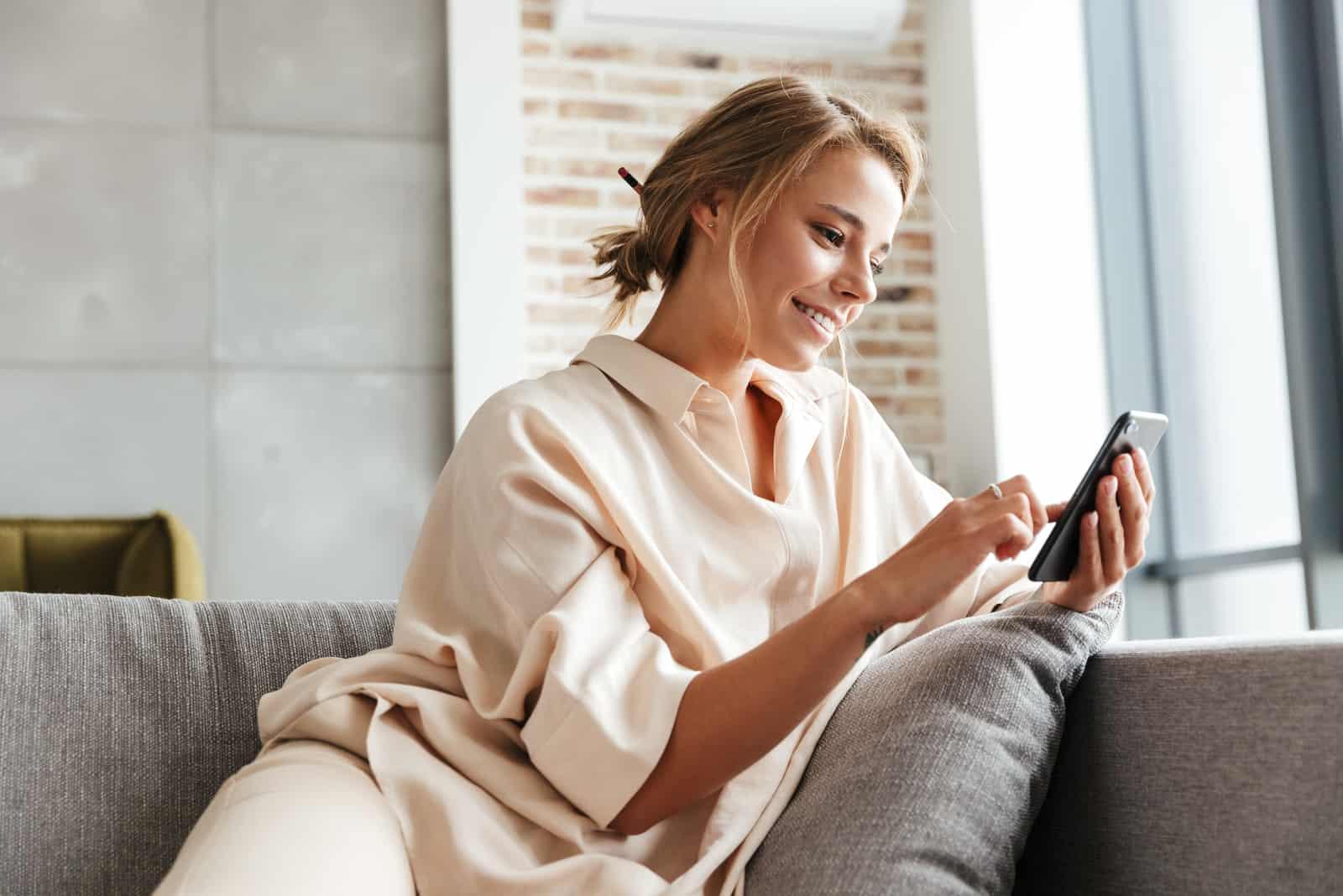 Une femme aux cheveux bruns souriante est assise sur le canapé et les touches du téléphone