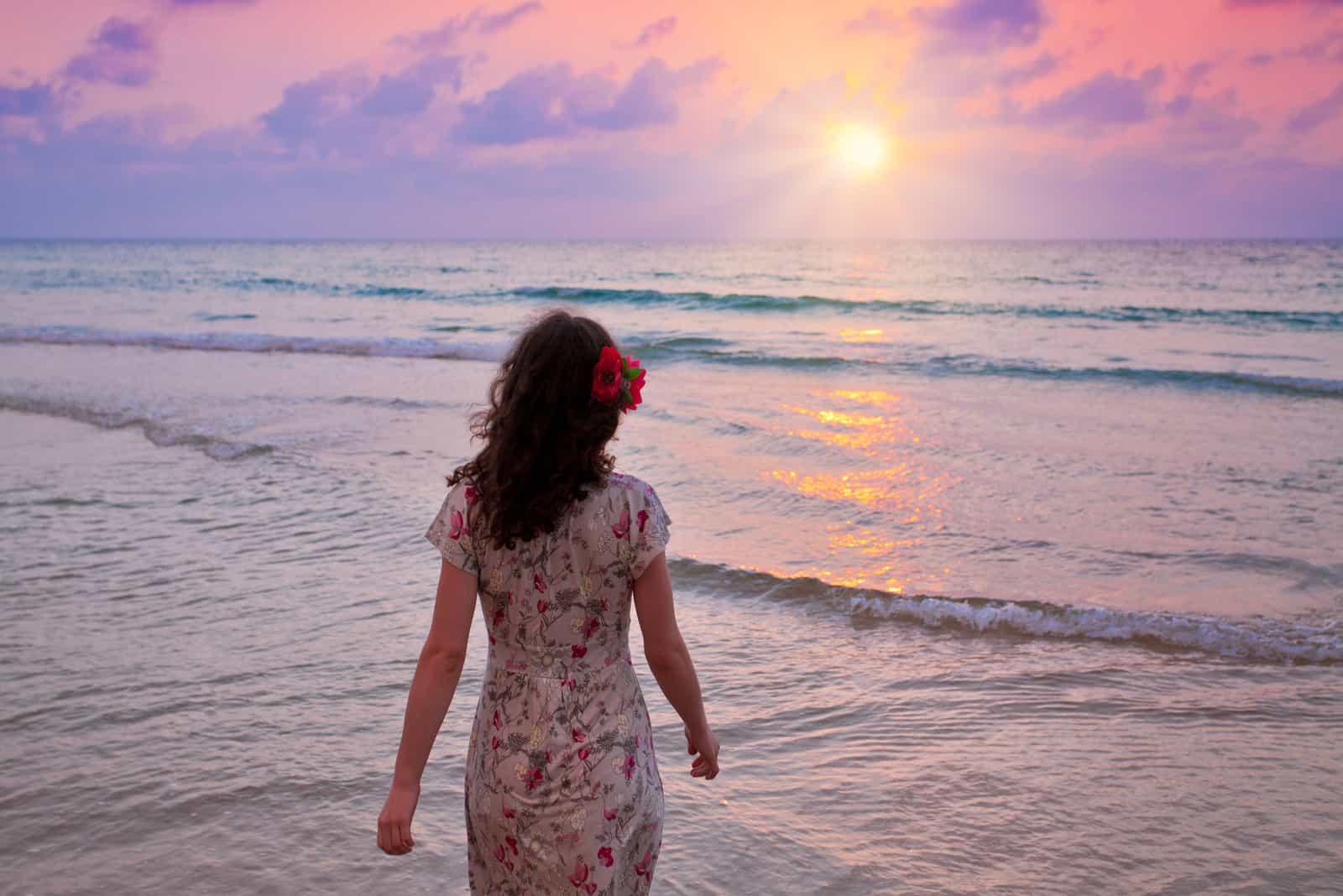 Une femme aux longs cheveux bruns se promène le long de la plage juste au bord de la mer