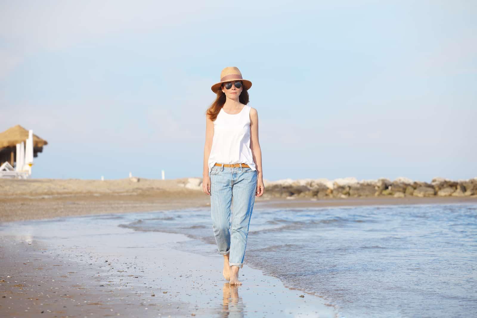 Une jeune femme aux longs cheveux bruns avec un chapeau sur la plage