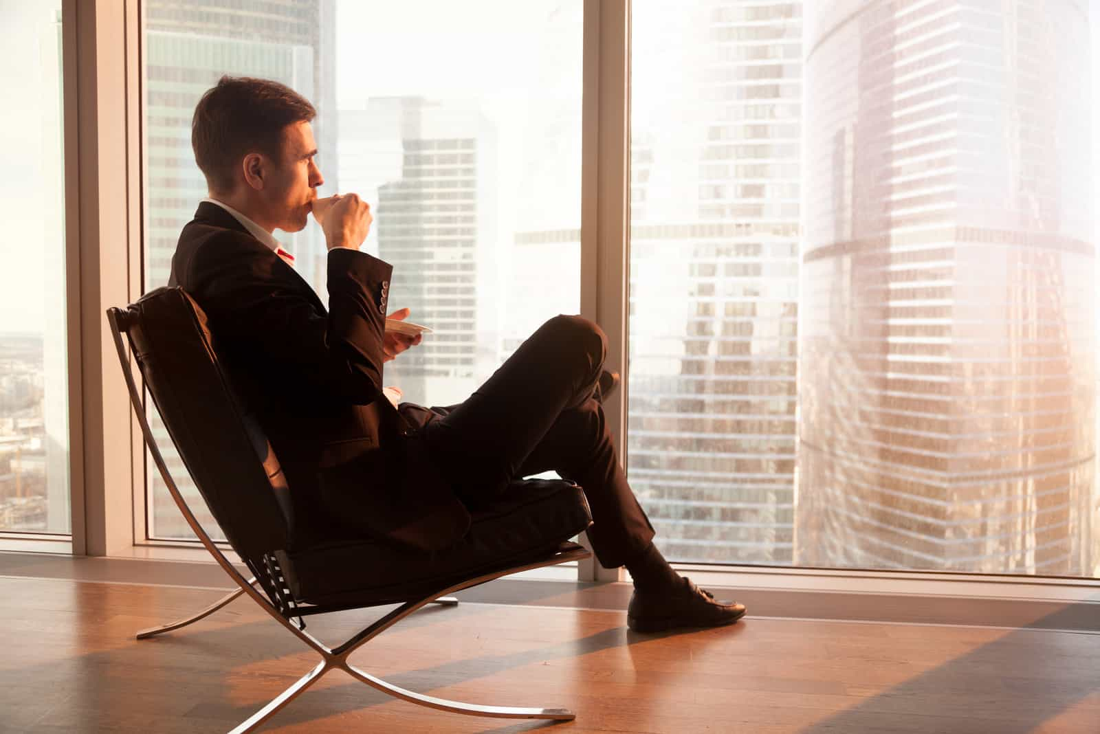 Vue latérale du bel homme d'affaires assis dans une chaise de bureau confortable, appréciant une tasse de café