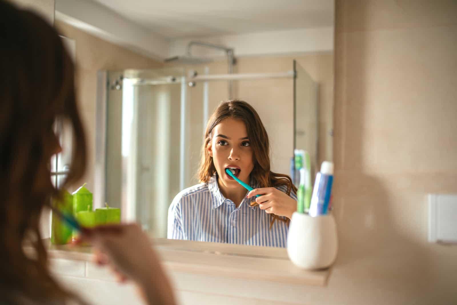 belle femme se brosser les dents et regarder dans le miroir