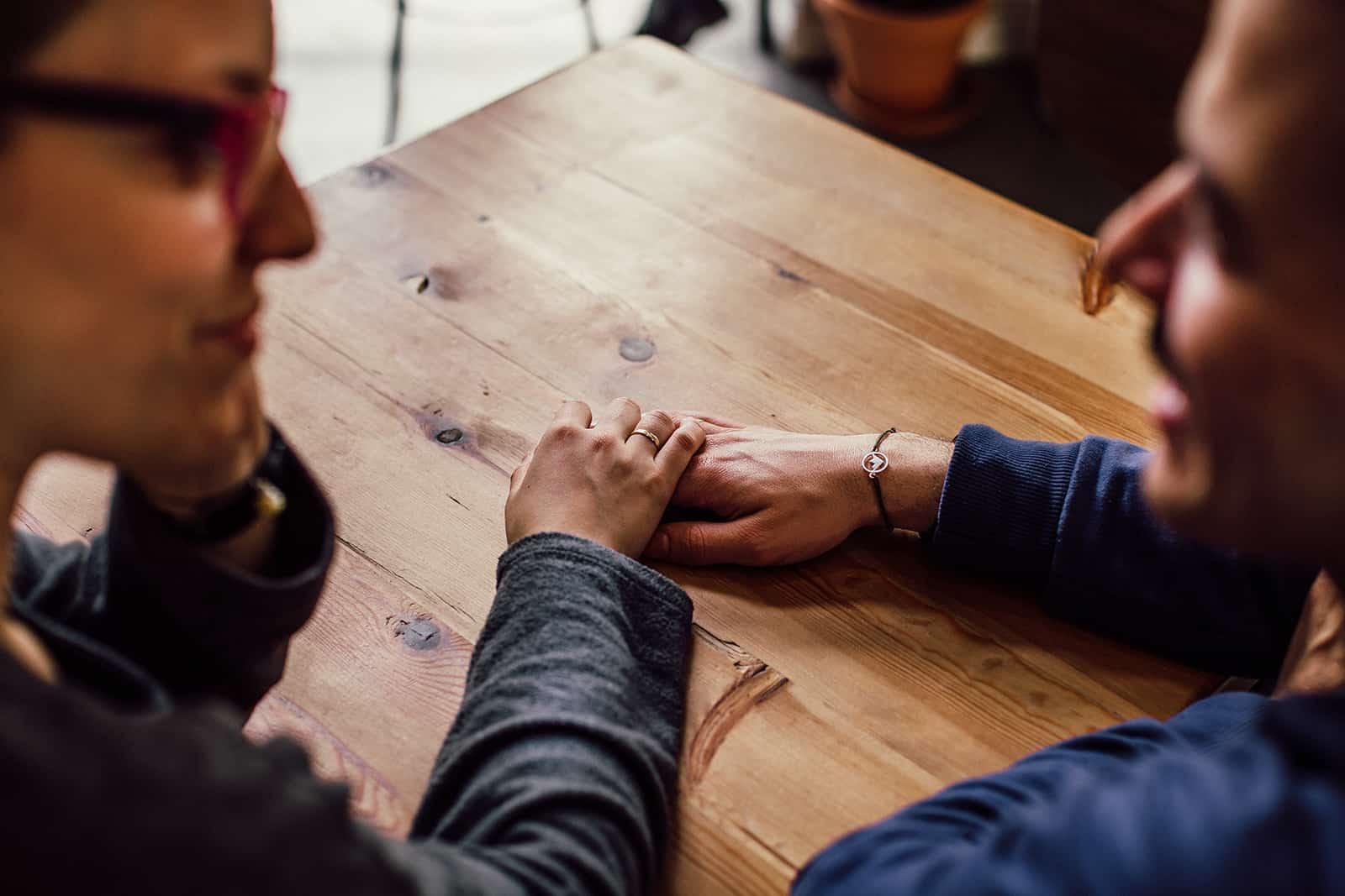 couple aimant se tenant la main et assis à la table