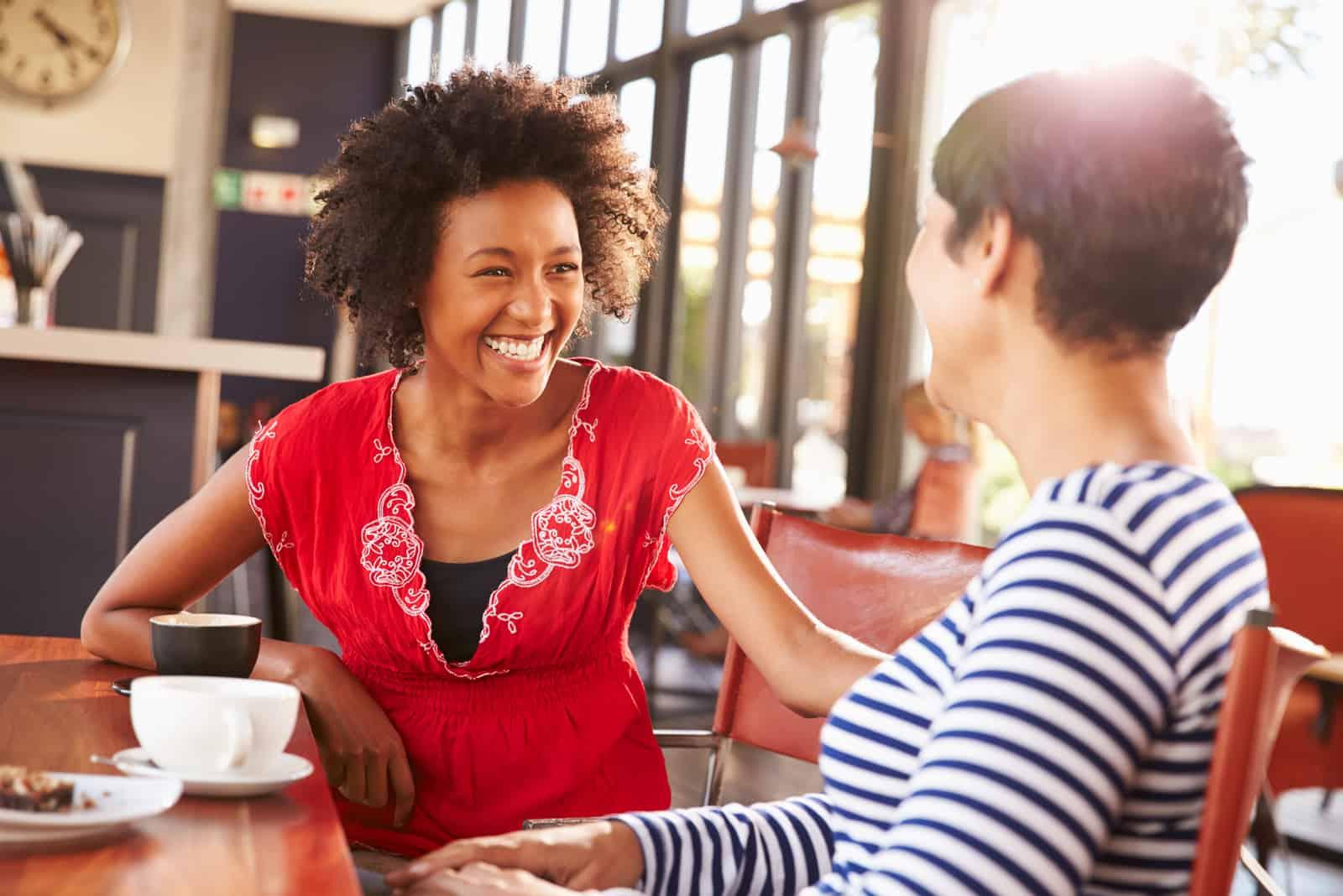 des amis s'assoient dans un café et parlent et rient