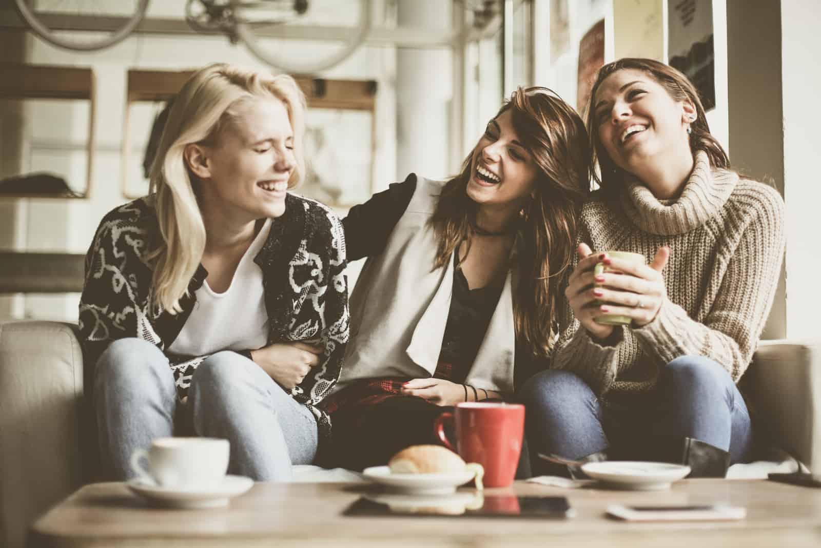 des amis s'assoient dans un café et rient