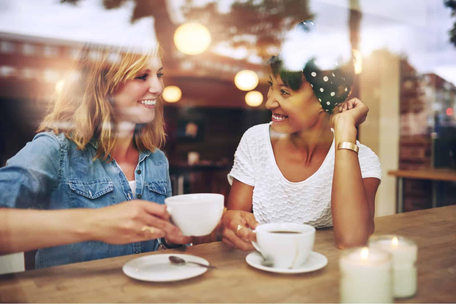 des amis sont assis en train de boire du café et de rire