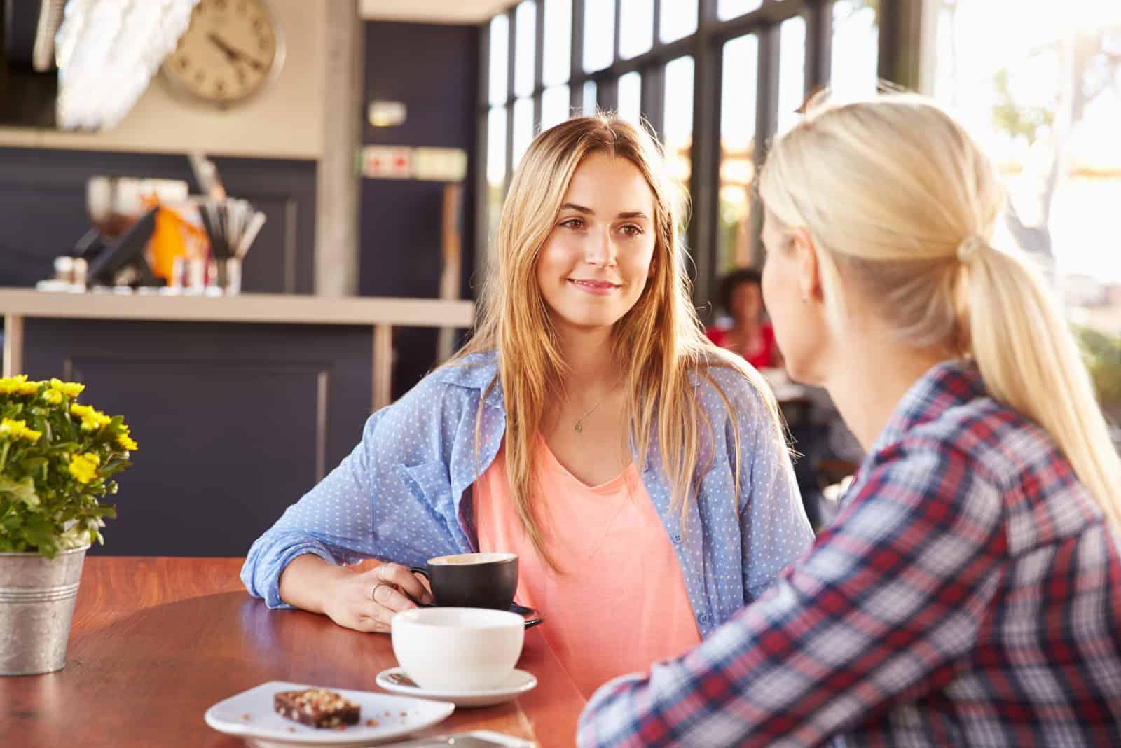 deux amis s'assoient et parlent autour d'un café