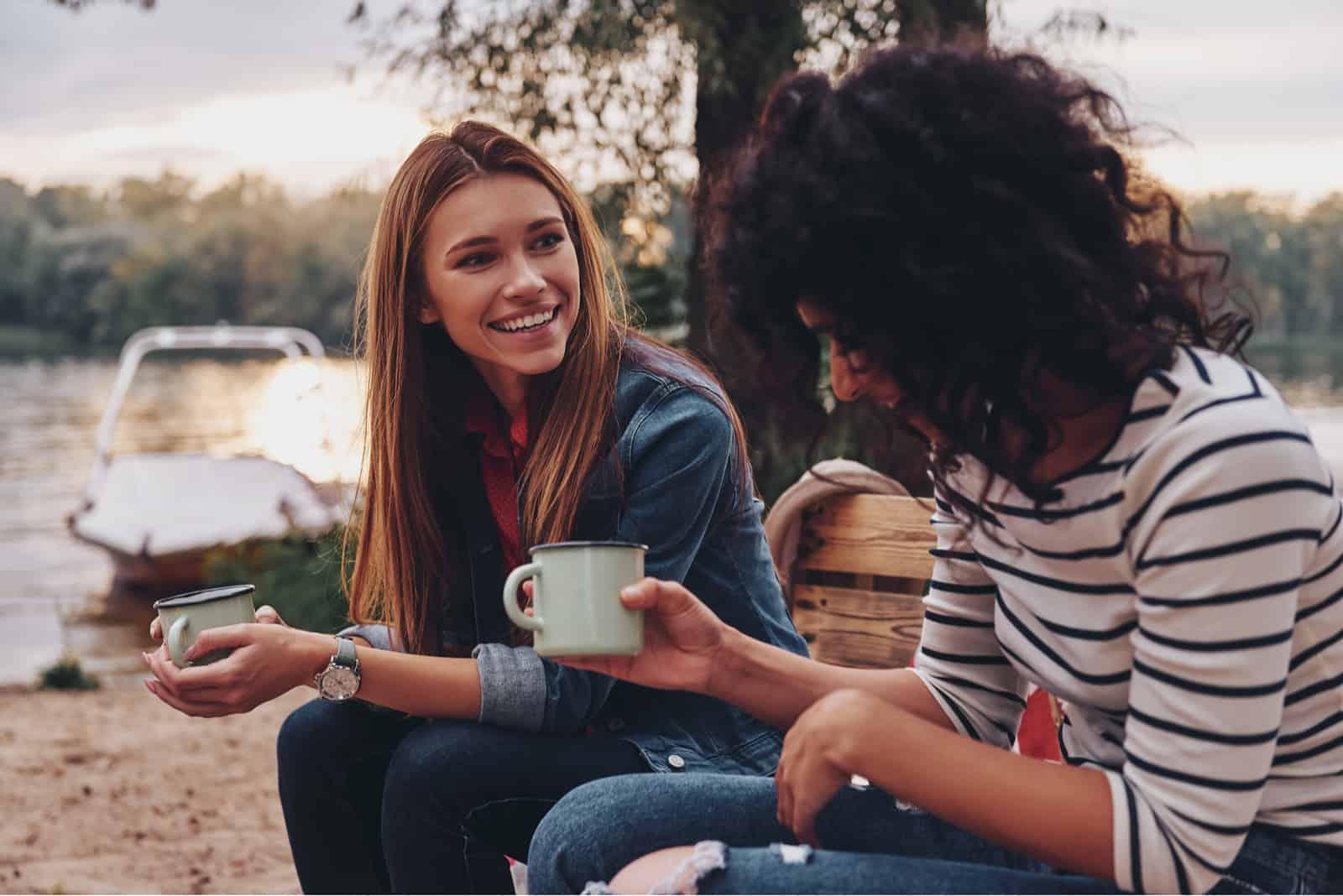 deux amis s'assoient et parlent tout en tenant des tasses de café dans leurs mains