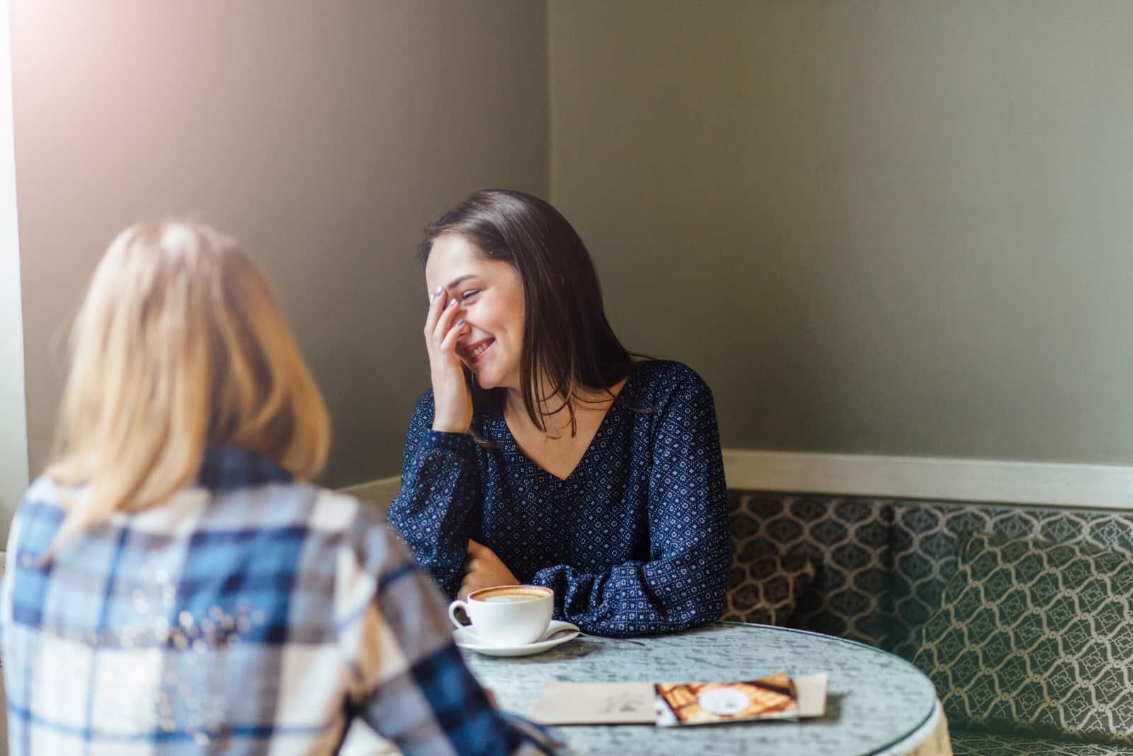 deux amis sont assis dans un café en train de boire du café et de rire