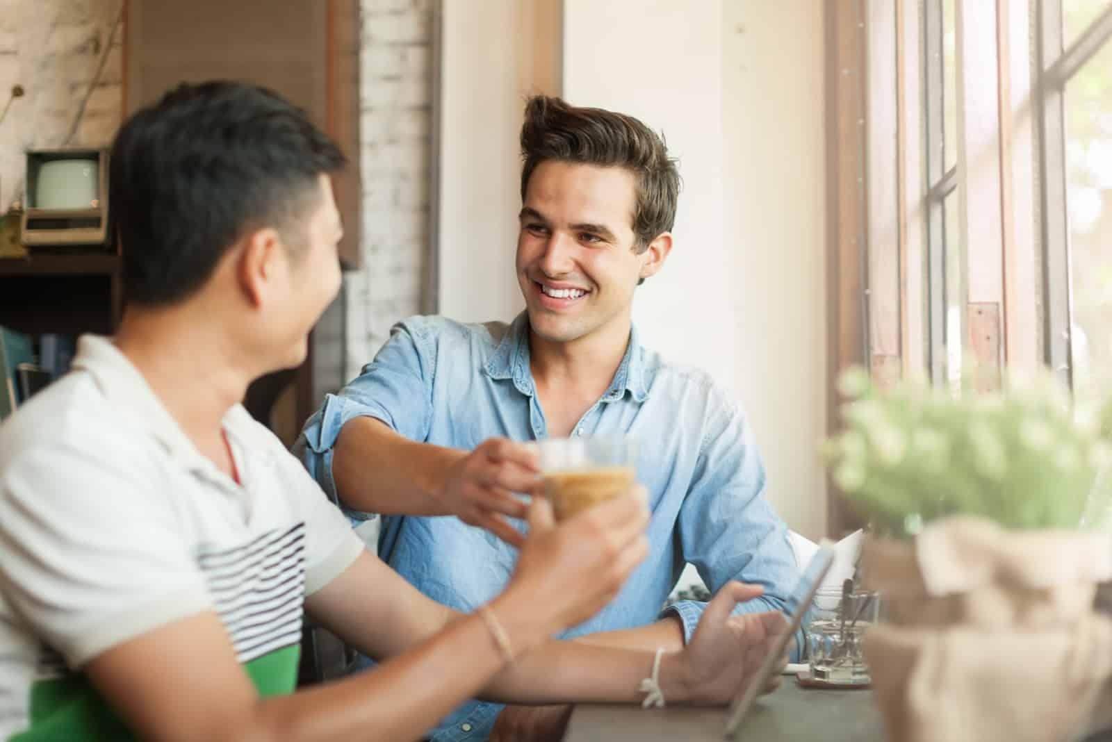 deux amis sont assis dans un café et boivent du café