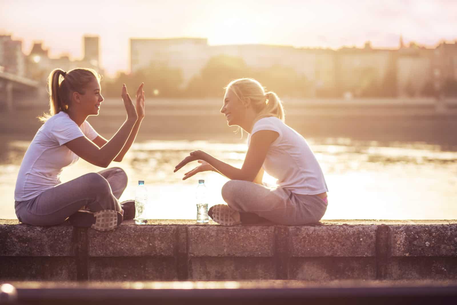 deux amis sont assis sur le mur et jouent