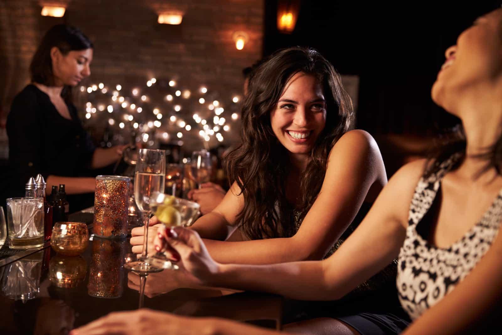 deux filles souriantes s'assoient derrière un traîneau et boivent