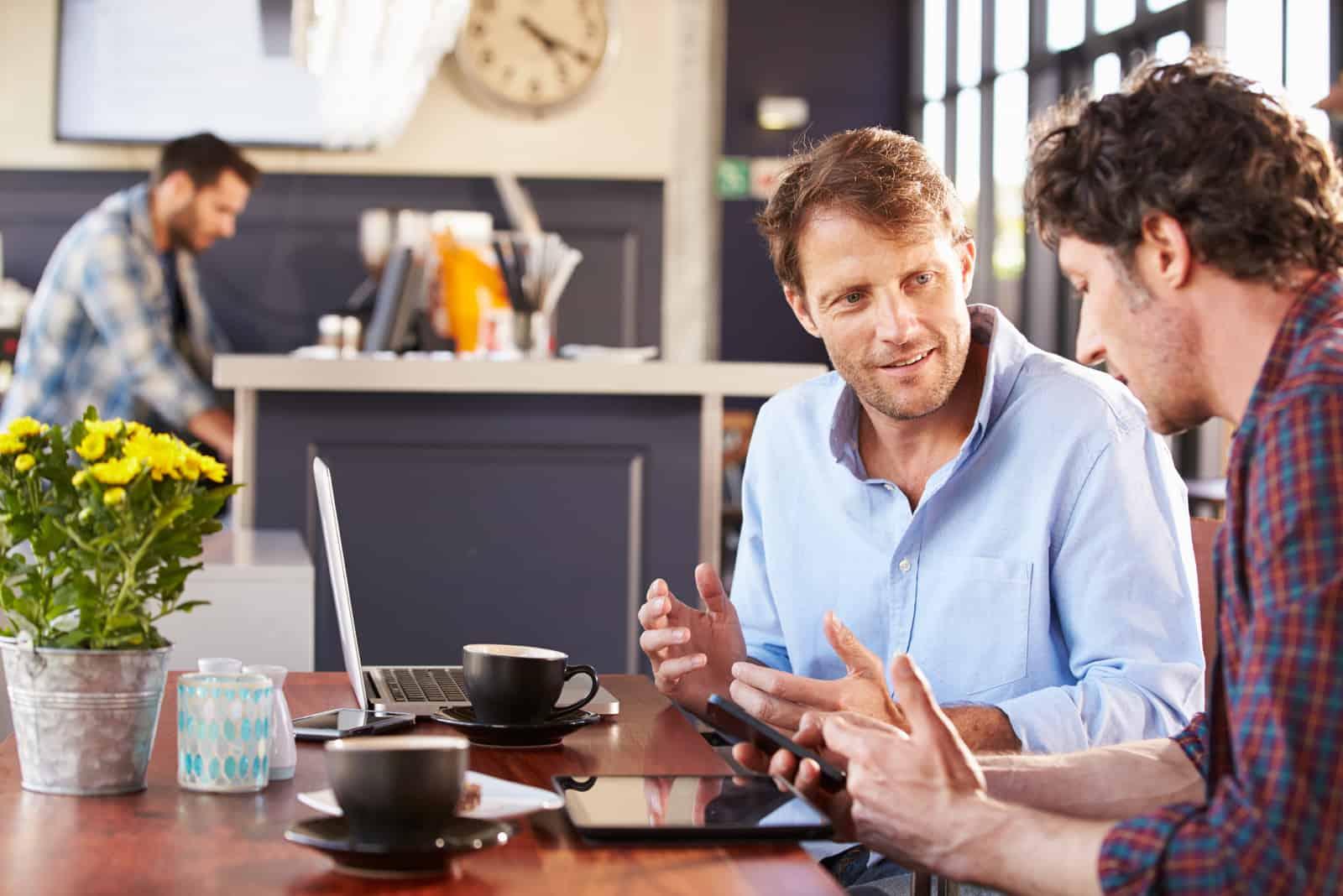 deux hommes sont assis à une table et parlent
