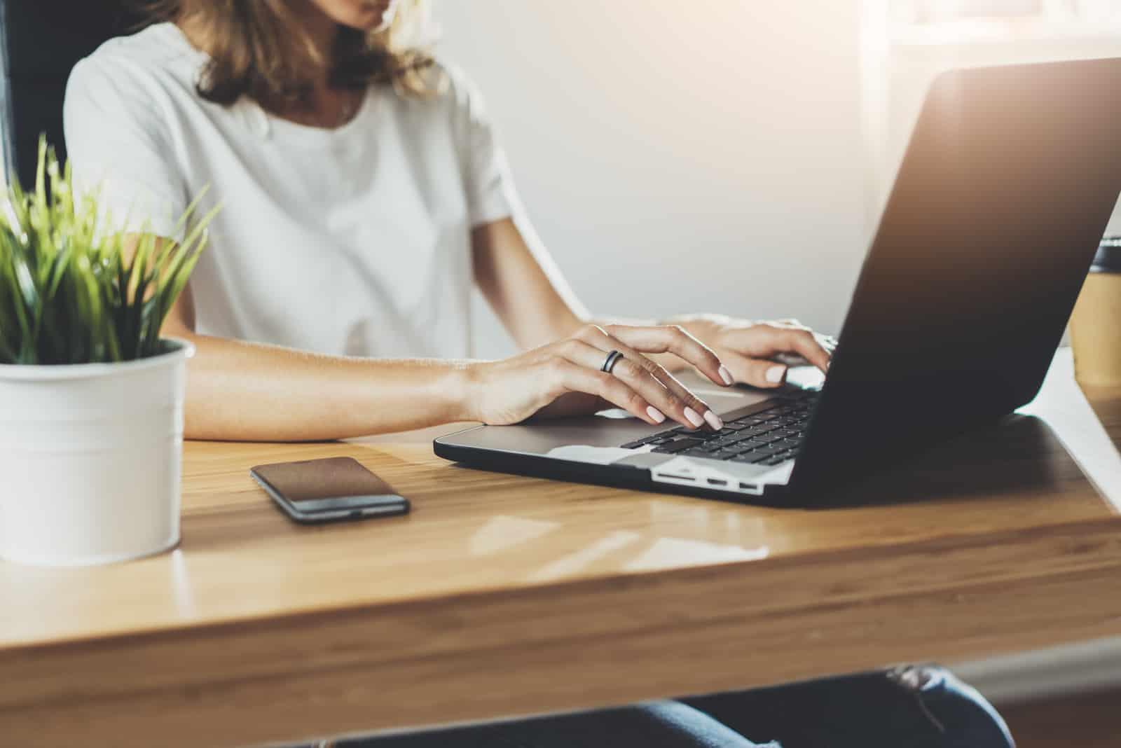 femme assise et bouton sur ordinateur portable