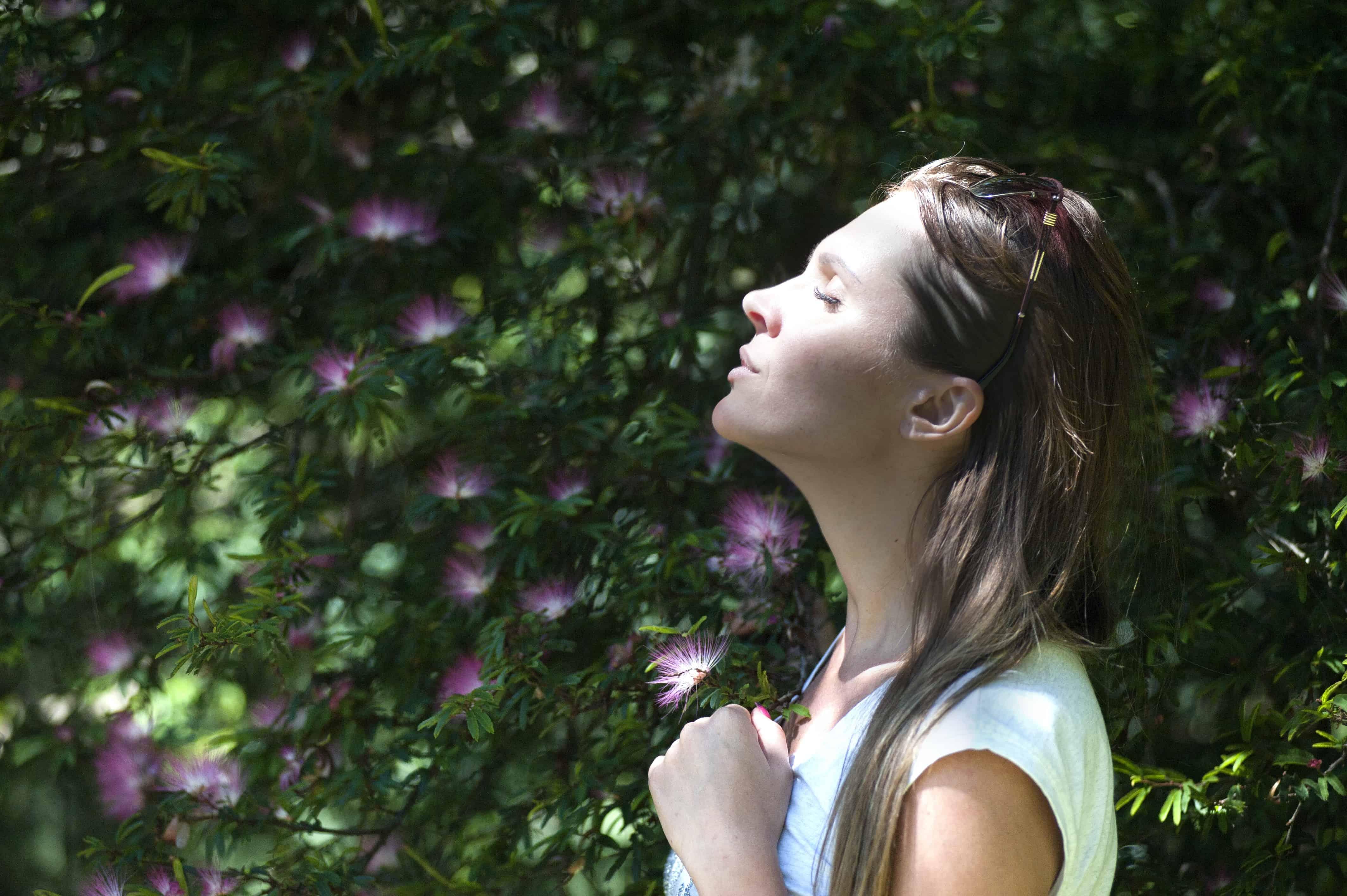 femme aux yeux fermés face au soleil debout dans le jardin
