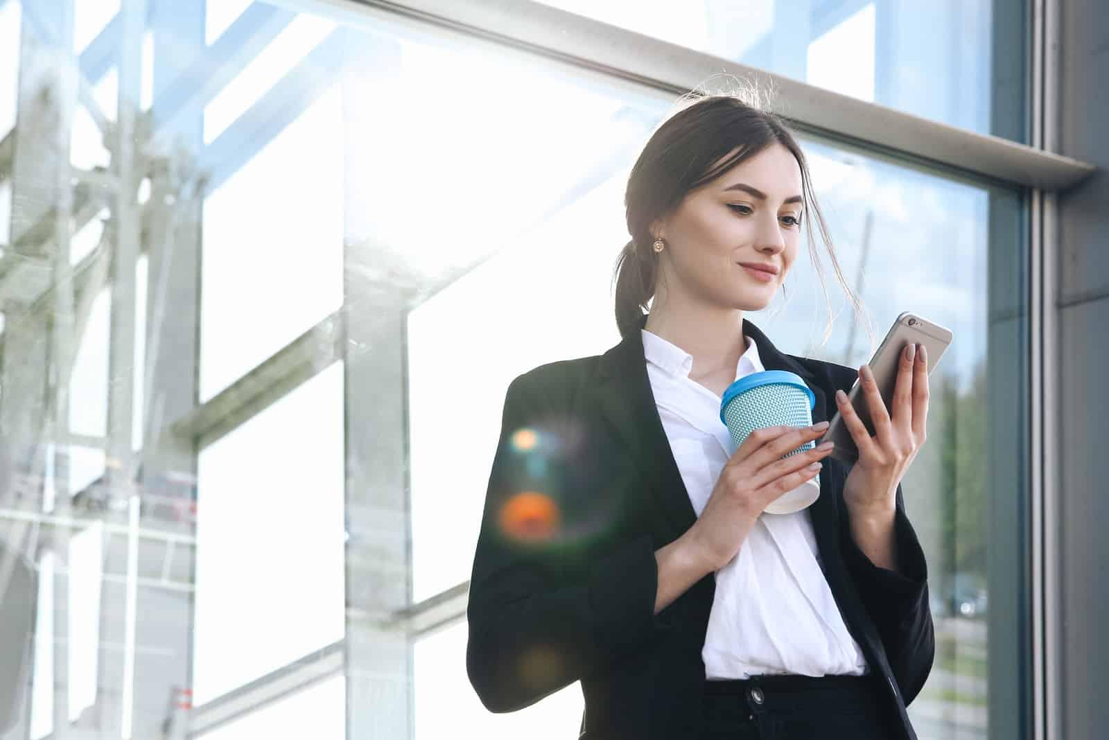 femme debout avec café à la main et bouton sur téléphone