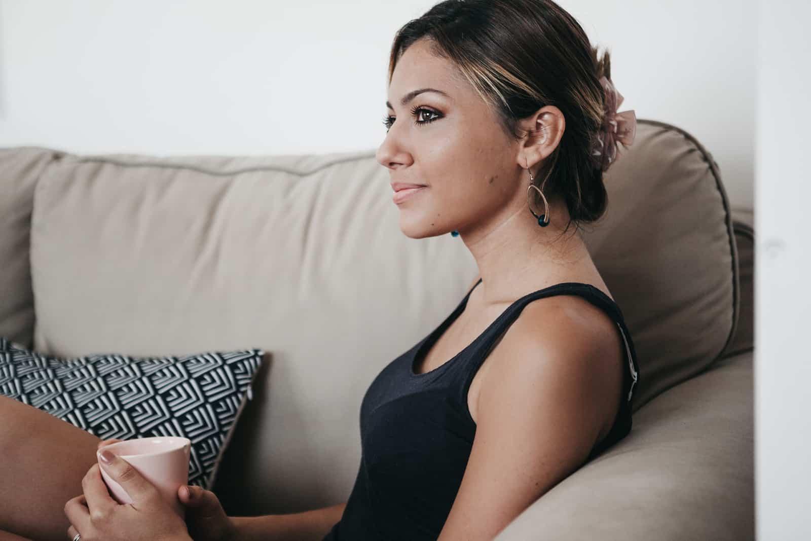 femme positive, boire du café sur le canapé et penser