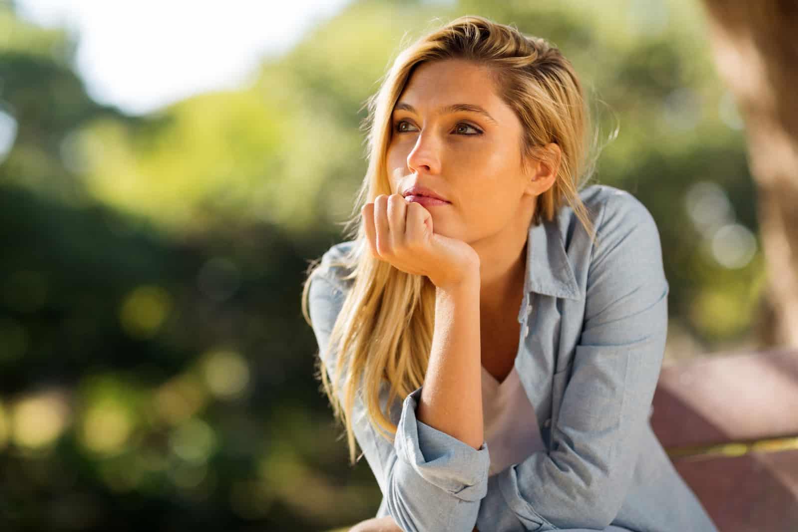 femme réfléchie assise seule à l'extérieur