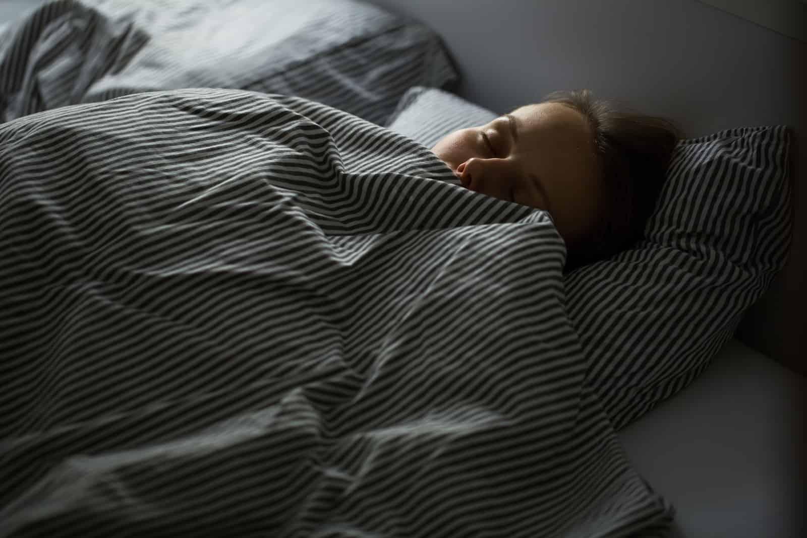 la jeune fille endormie s'est bourrée d'une couette