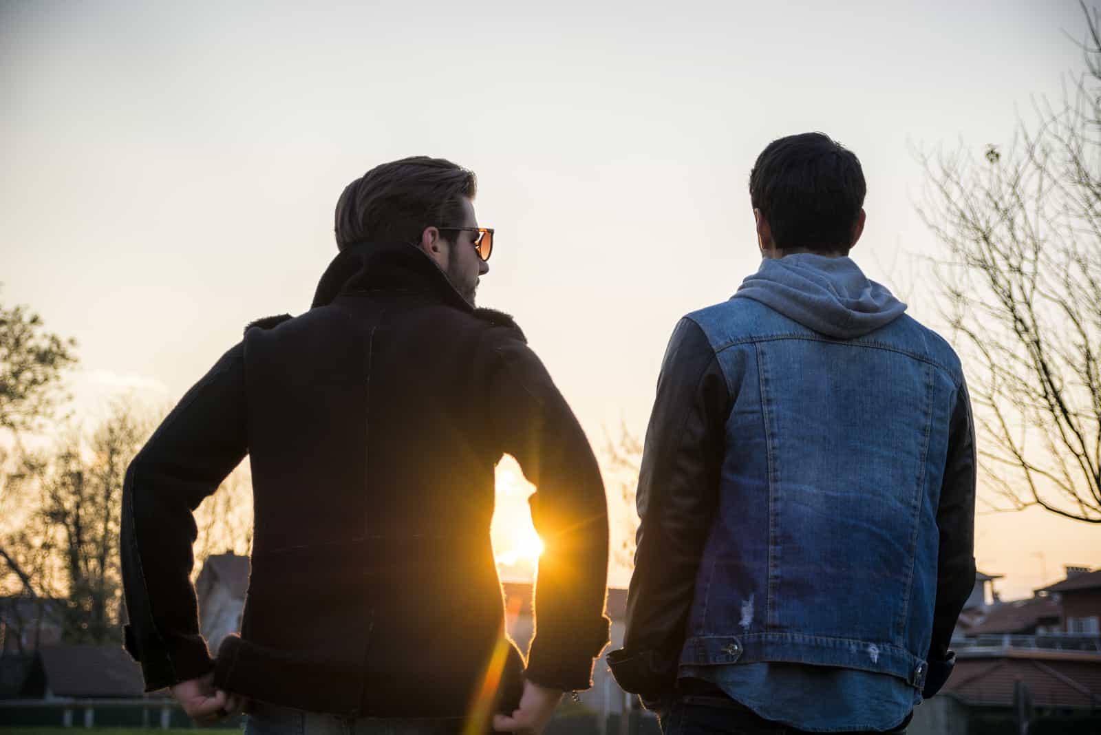 les deux hommes se tiennent le dos tourné et parlent
