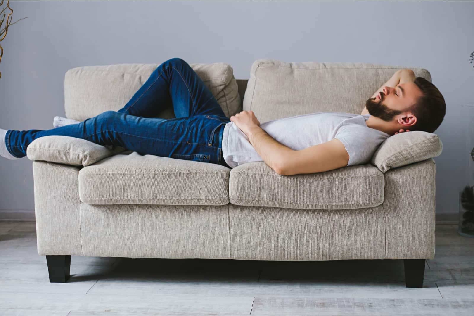 l'homme est allongé sur le canapé les yeux fermés