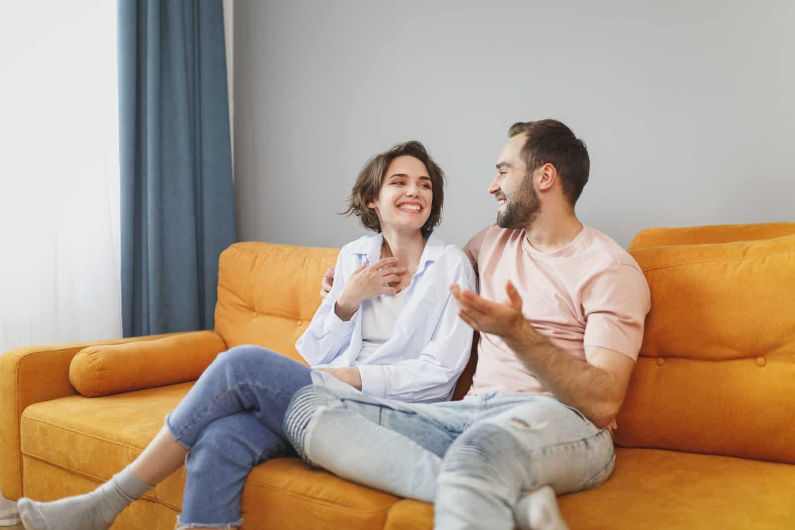 l'homme et la femme sont assis sur le canapé en s'embrassant et en riant