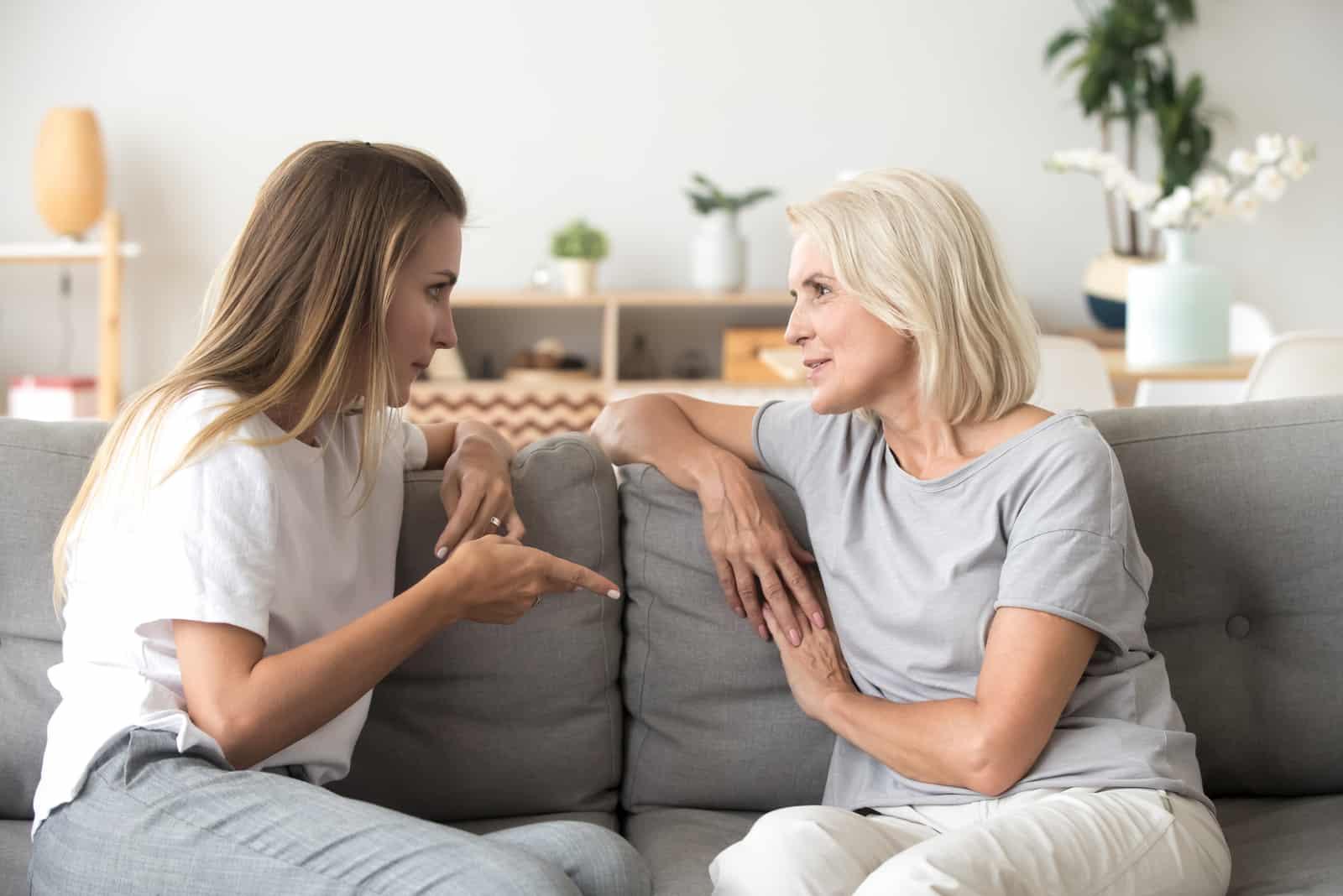 mère et fille s'assoient sur le canapé et parlent