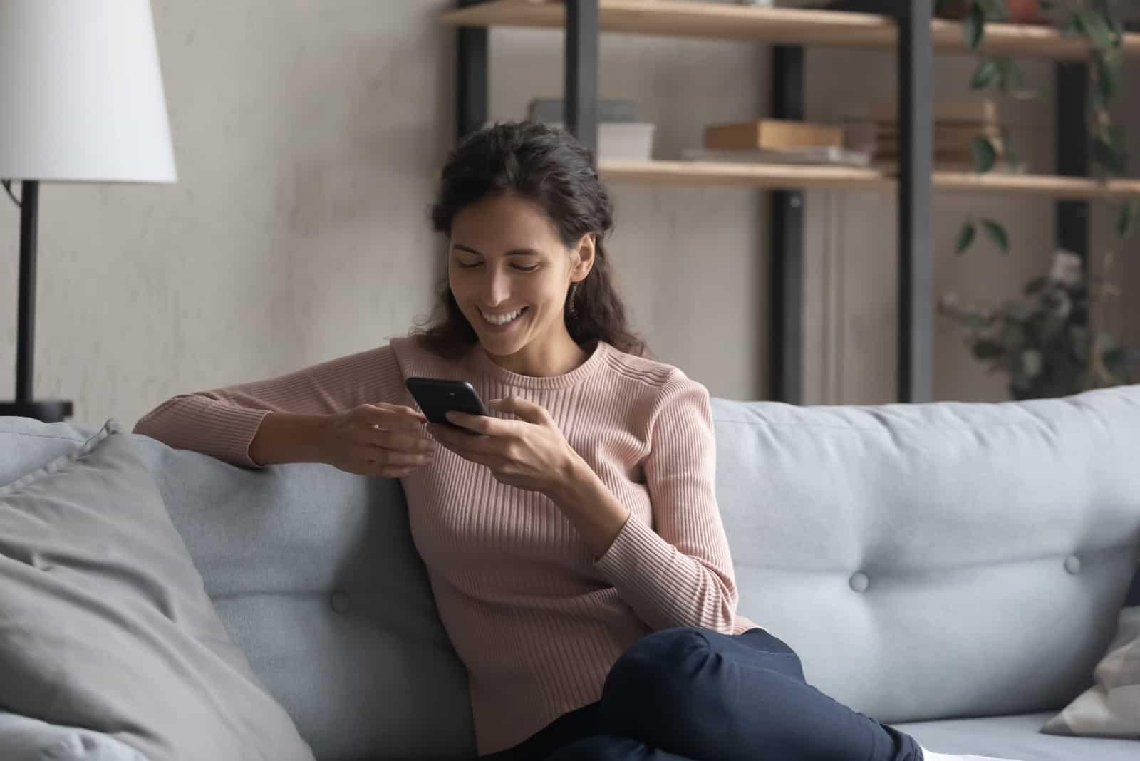 smiling millennial girl using cellphone