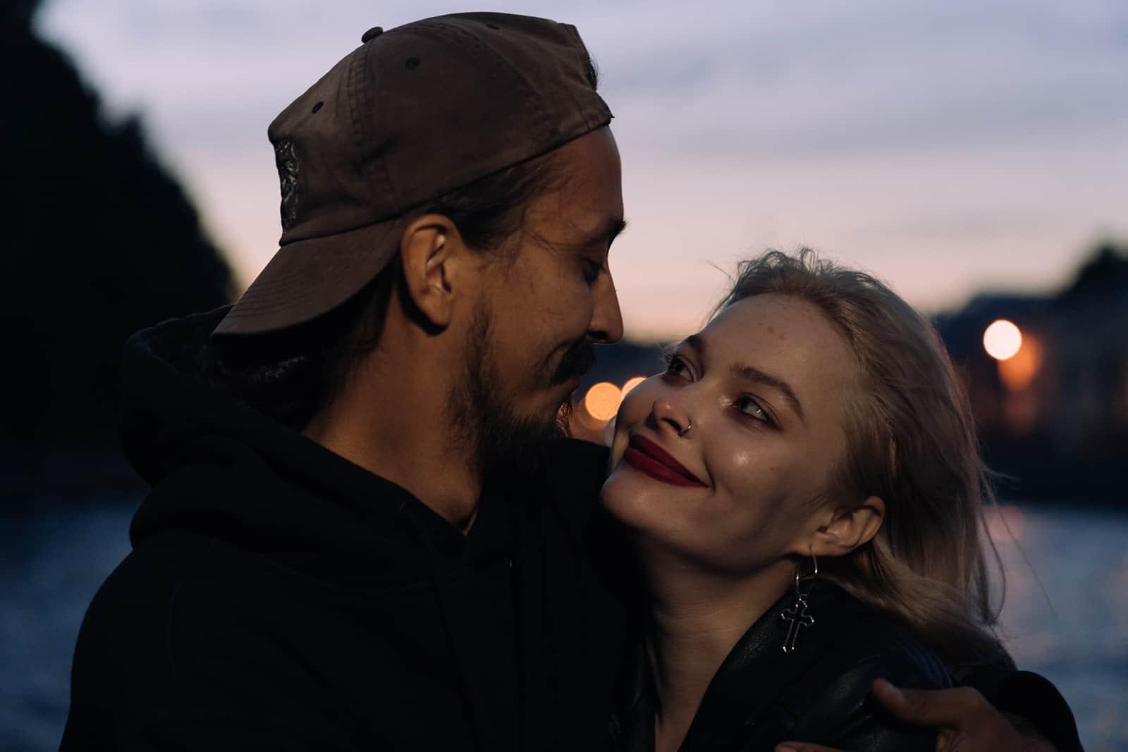 un couple amoureux se regardant tout en se serrant dans ses bras en plein air