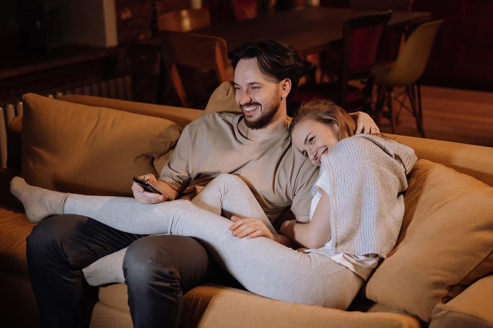 un couple heureux assis sur le canapé et câlins le soir