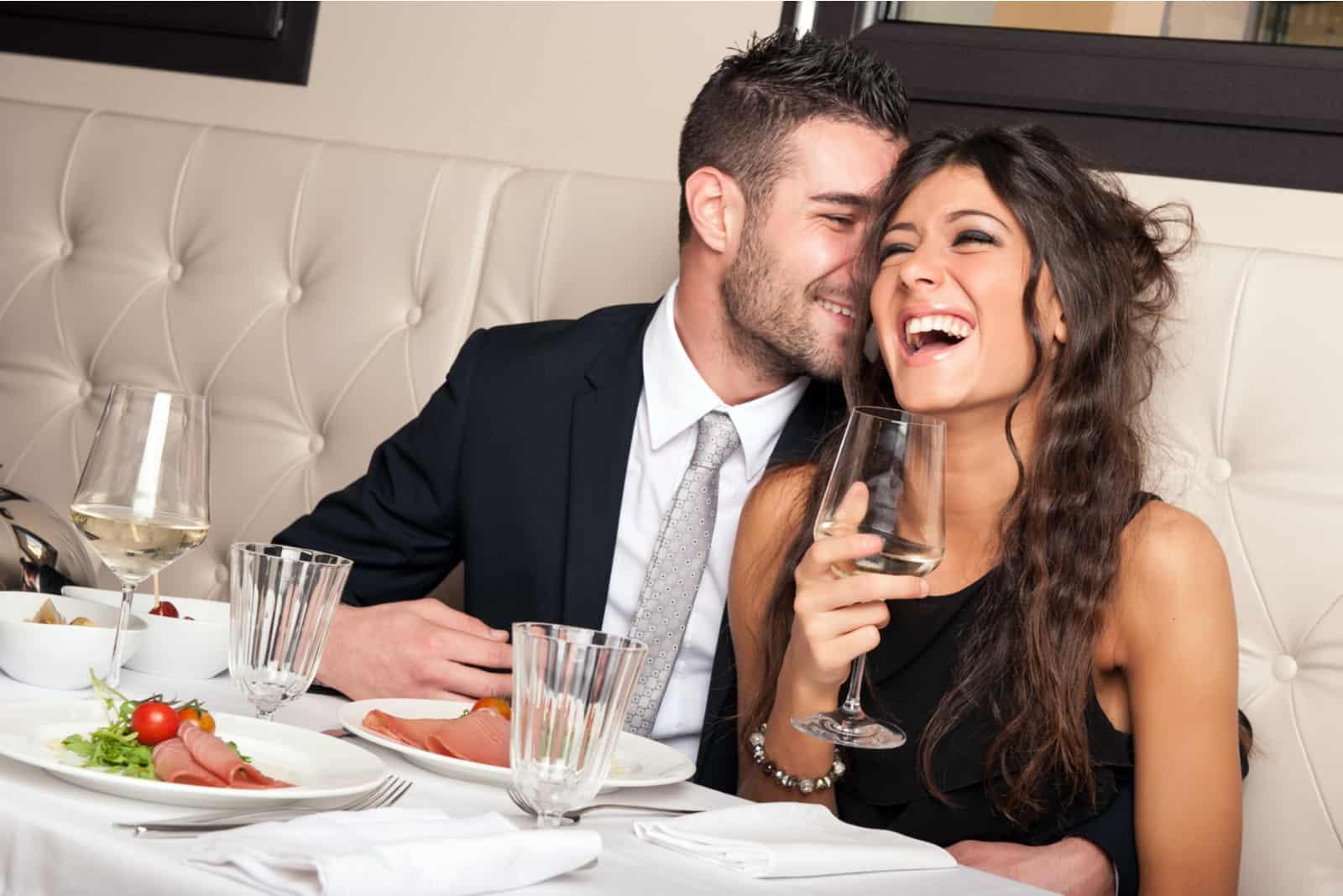 un couple souriant assis près du vin et riant