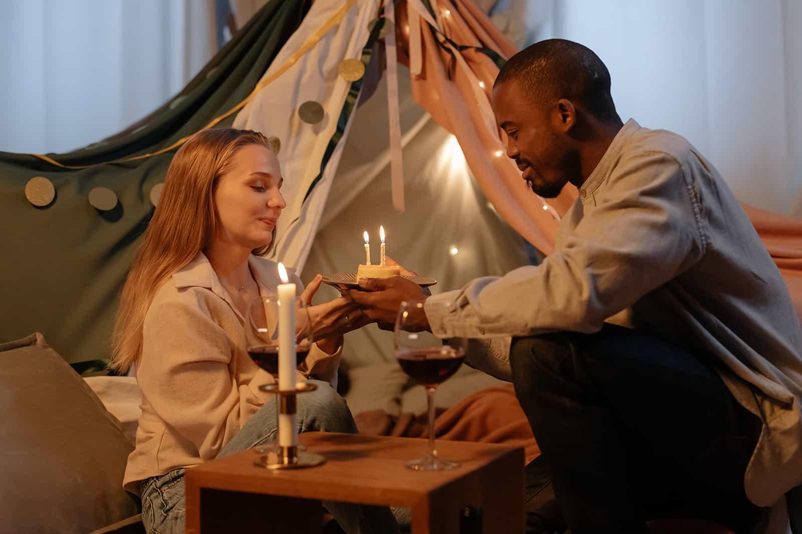 un couple tenant un gâteau avec des bougies à la maison
