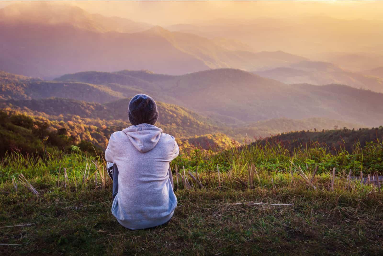 un homme assis sur l'herbe, le dos tourné