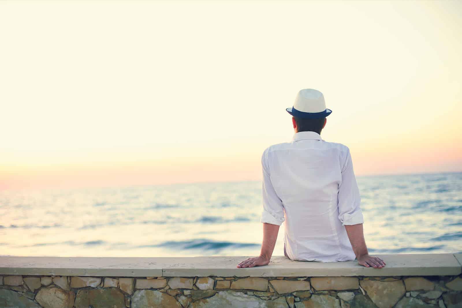 un homme avec un chapeau sur la tête est assis et regarde le coucher du soleil
