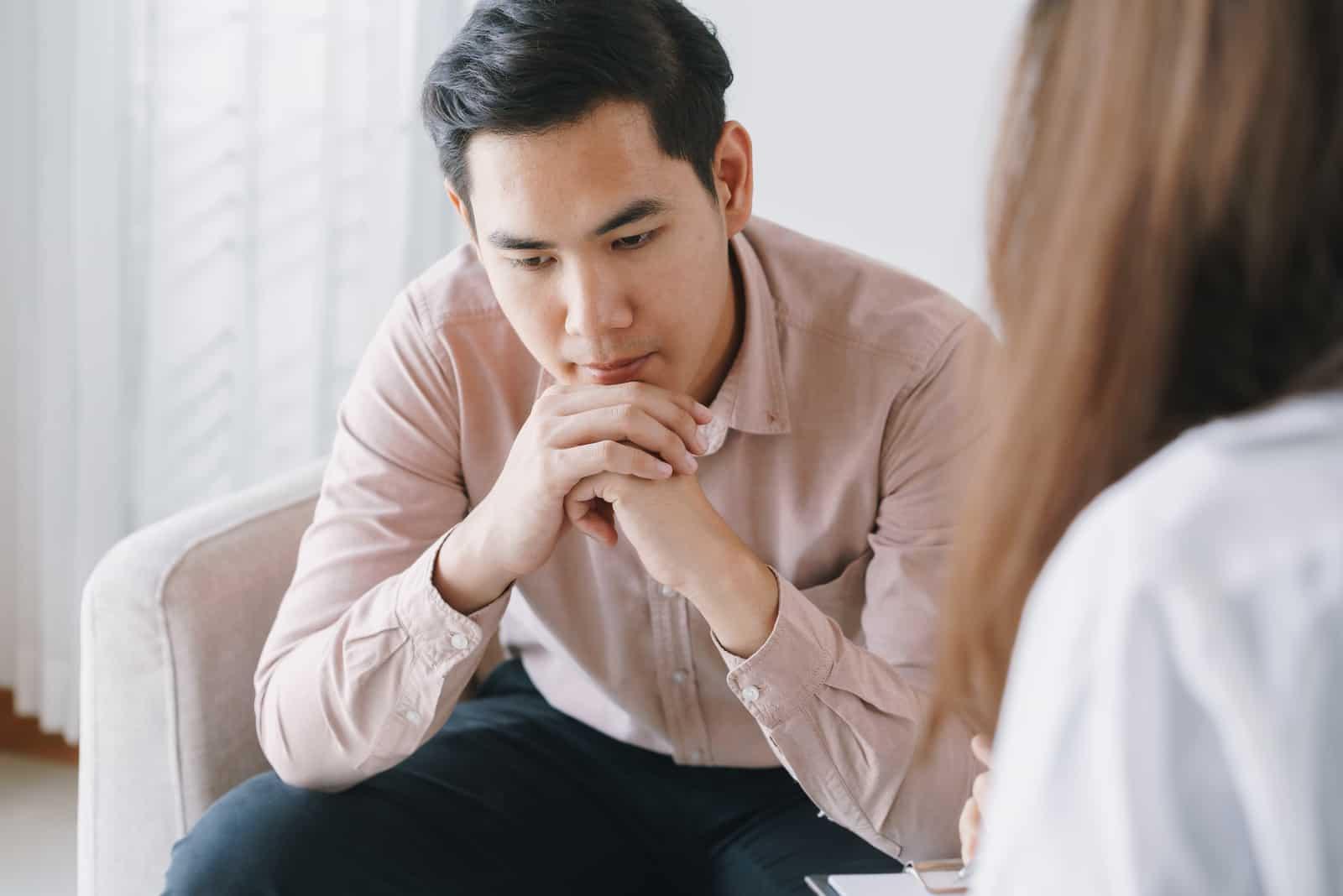 un homme déçu est assis avec une femme et ils parlent