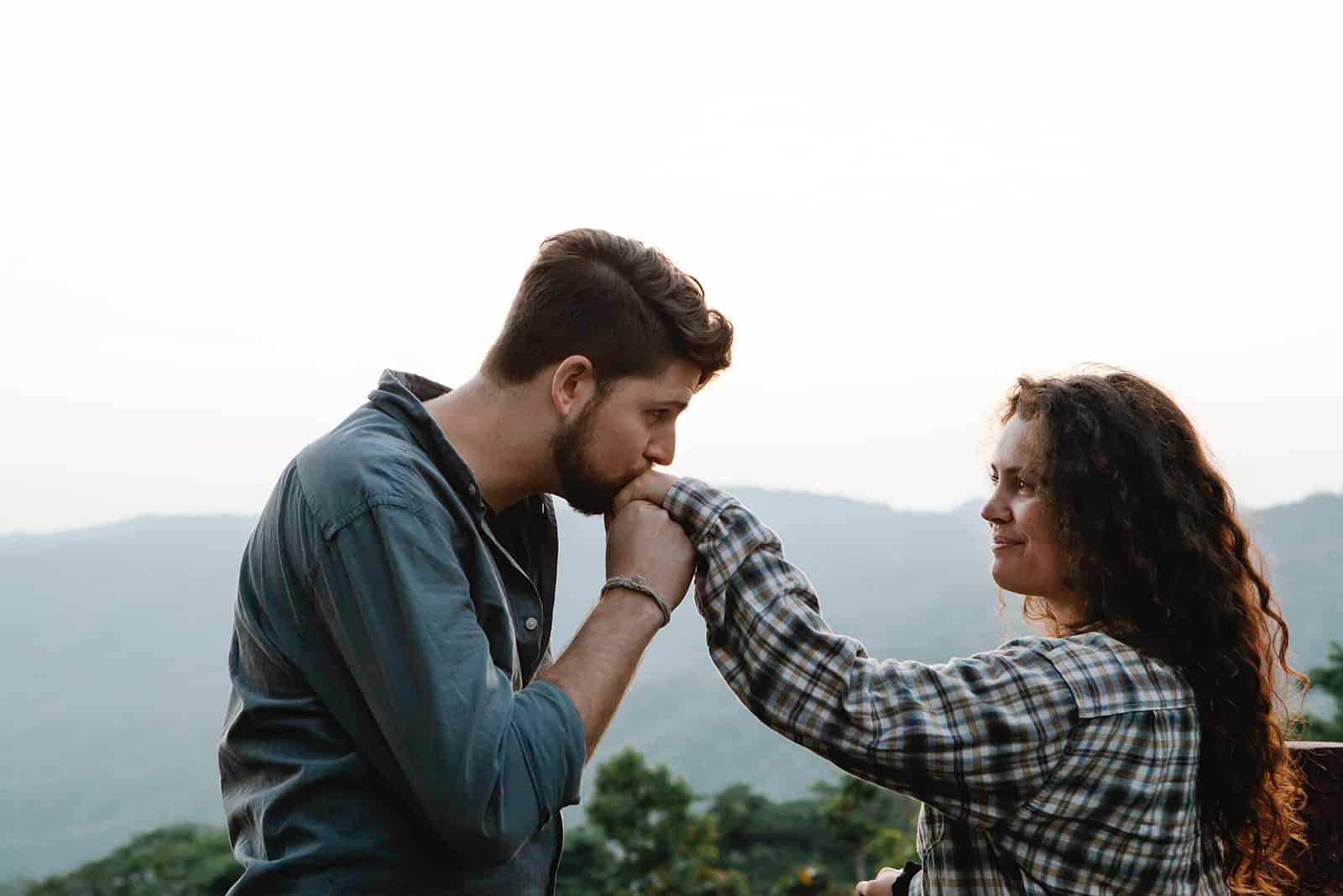 Un homme embrassant la main de sa petite amie souriante en se tenant debout dans la nature