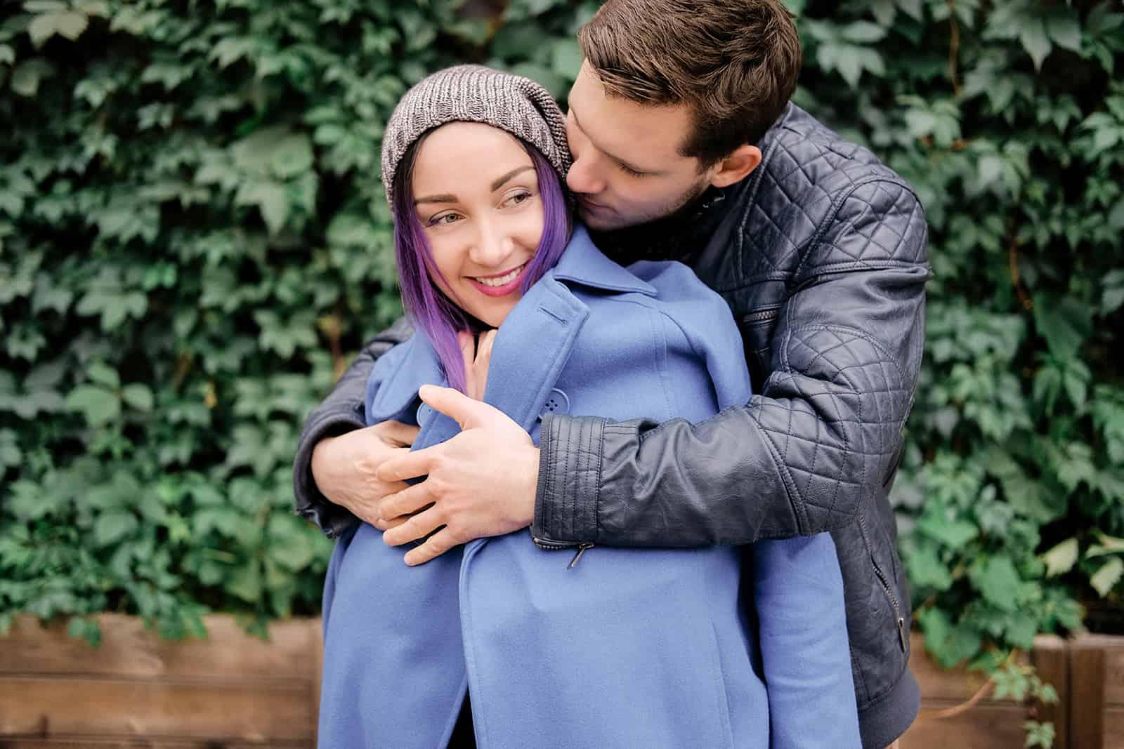 un homme embrassant une femme à l'arrière tout en se tenant à l'extérieur