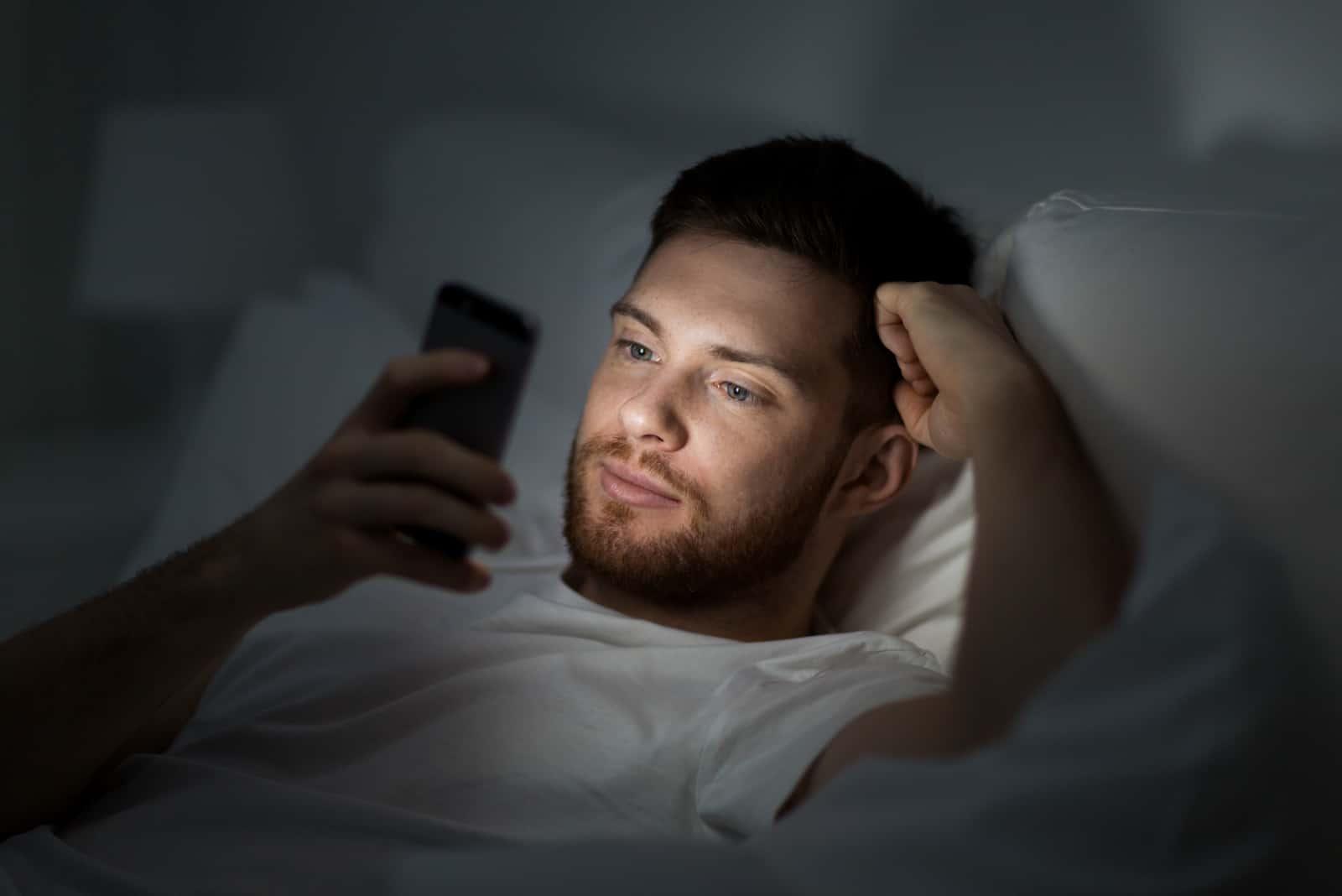 un homme est allongé dans son lit et un bouton sur le téléphone
