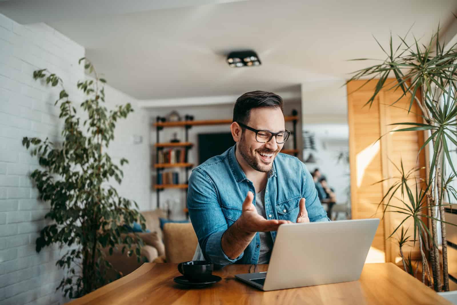 un homme est assis derrière un ordinateur portable et rit