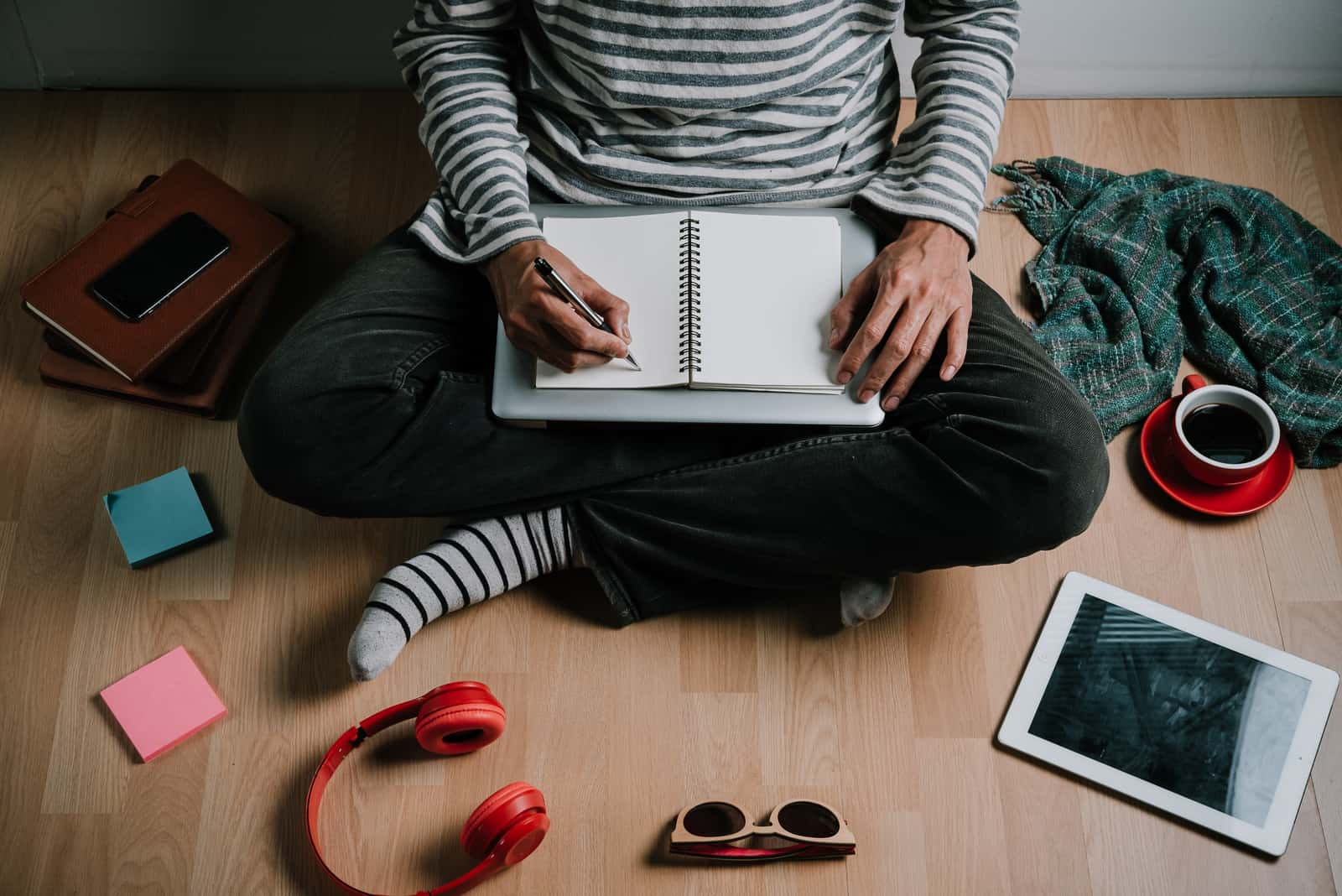 un homme est assis par terre et écrit